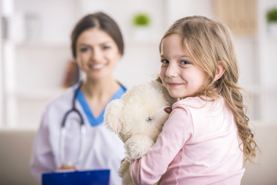 young girl smiling while holding her teddy bear