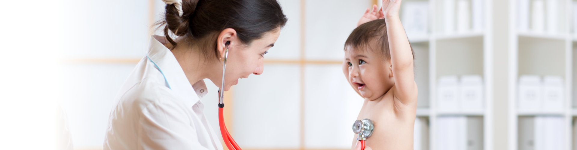 nurse using her stethoscope on a toddler